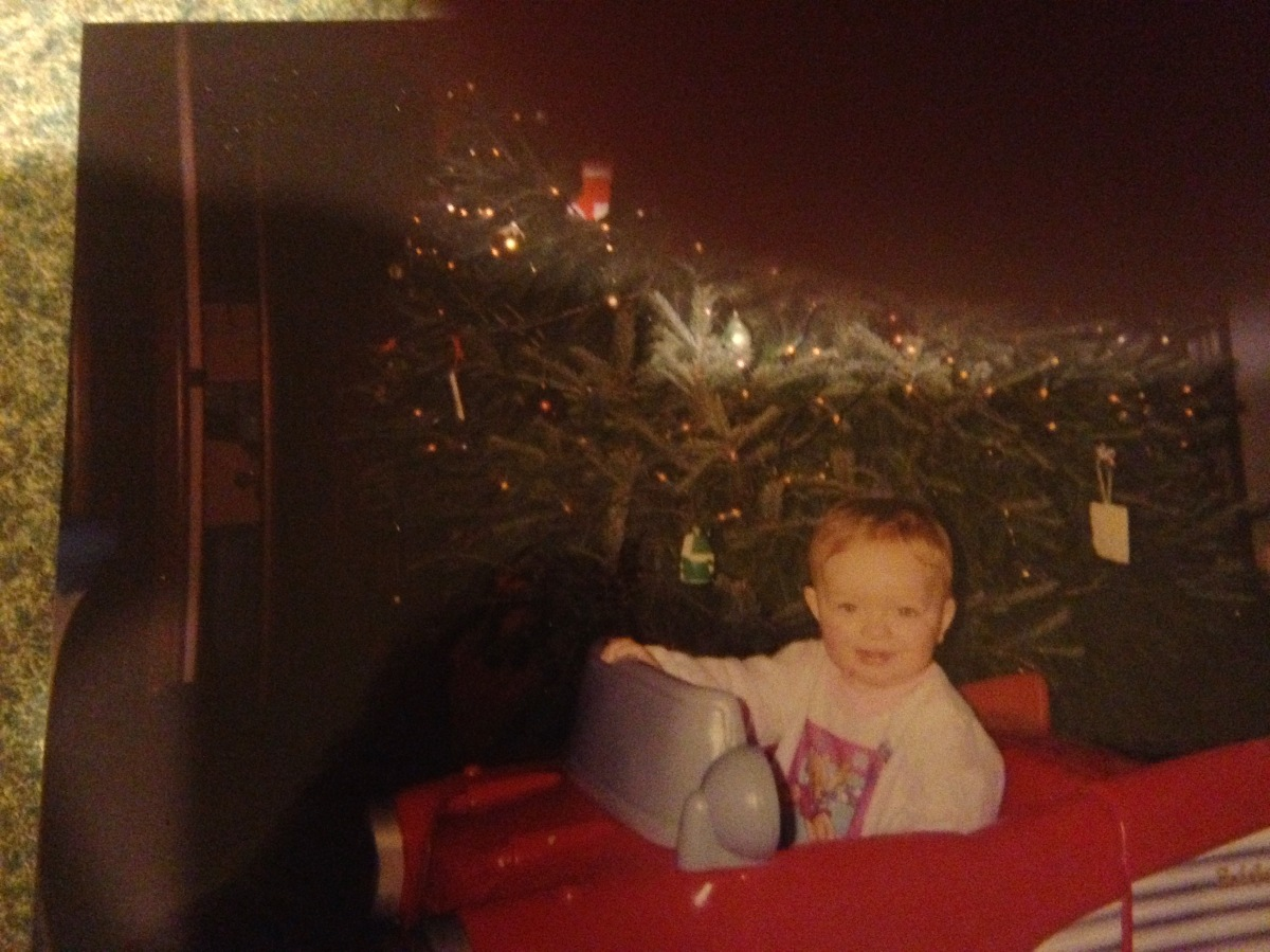 A white, strawberry-blonde toddler sits in a plastic toy red car beneath a Christmas Tree.