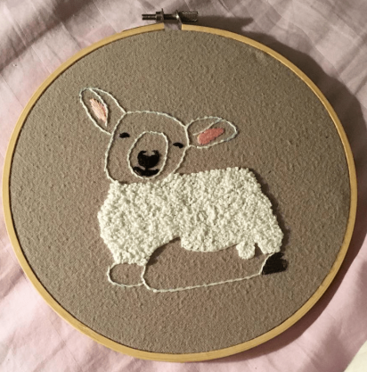 Embroidery of a peaceful, resting sheep. Its body is made of tightly-crocheted white yarn, left an outline around its head and feet and filled in on its midsection. Its outlined ears are pink inside and its eyes, nose, mouth, and hooves are filled in with black yarn, which stands out against the brown background stretched across its hoop.