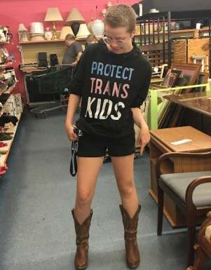 "Elliot poses in a shirt that reads ""protect trans kids,"" pointing at a pair of stylish brown cowboy boots."