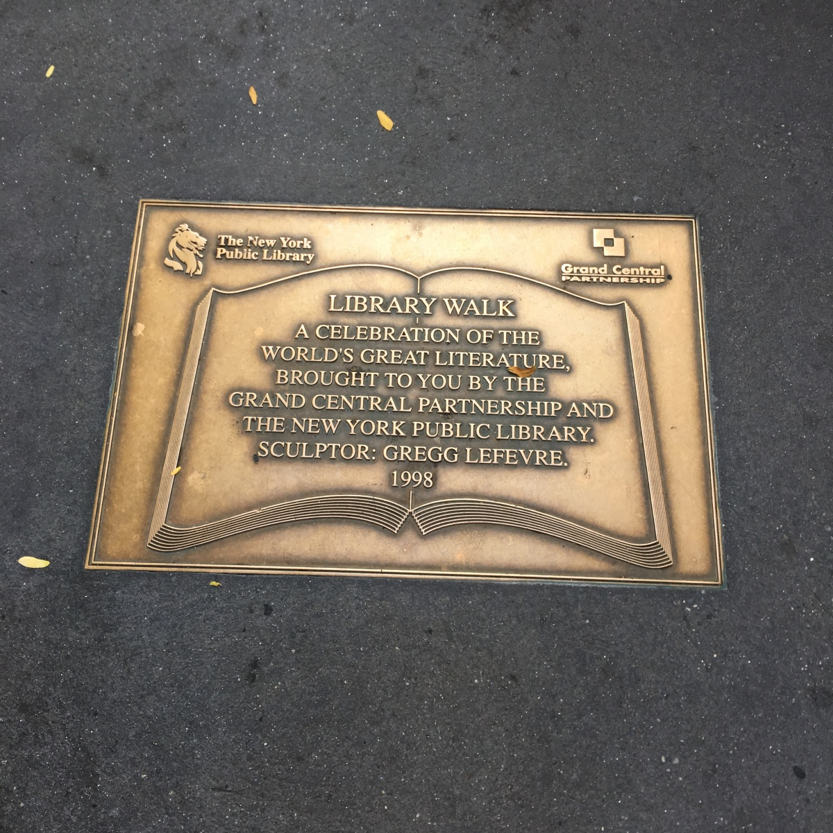 """Bronze-gold colored plaque embedded in a New York sidewalk.Its inscription reads: """"Library Walk. A celebration of the world's great literature, brought to you by the Grand Central Partnership and the New York Public Library. Sculptor: Gregg LeFevre. 1998."""