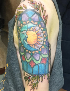 A pale upper arm, containing a rainbow-colored tattoo emulating a stained glass window. A circle whose left side is a moon and whose right is a sun sits at the window's upper center. Around the window stretch olive green leaves on branches also sporting small red berries.