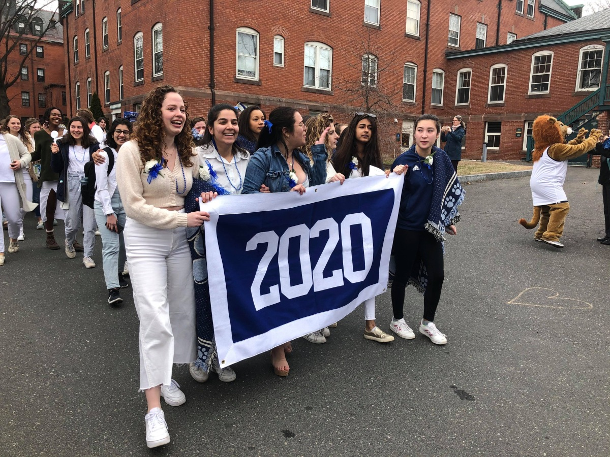 """Mount holyoke seniors parade past Safford Hall holding a blue and white """"2020"""" banner."""
