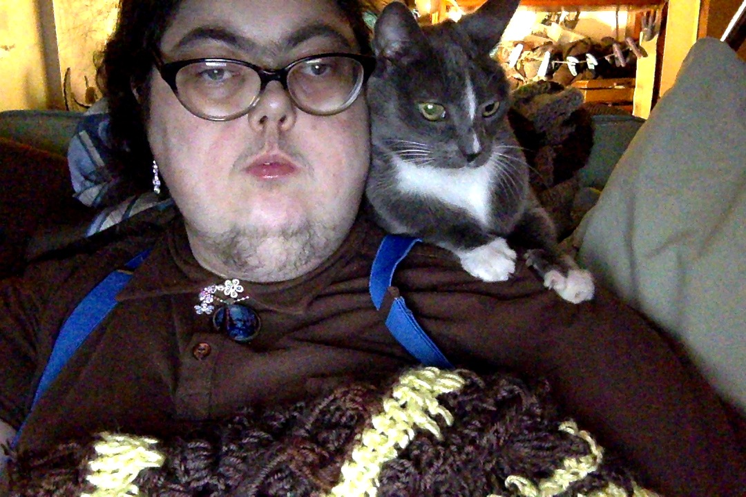 Mel Baggs, wearing glasses and a brown button-down shirt, faces the camera with a knitting project balanced on their chest. A grey and white cat sits perched on their shoulder.