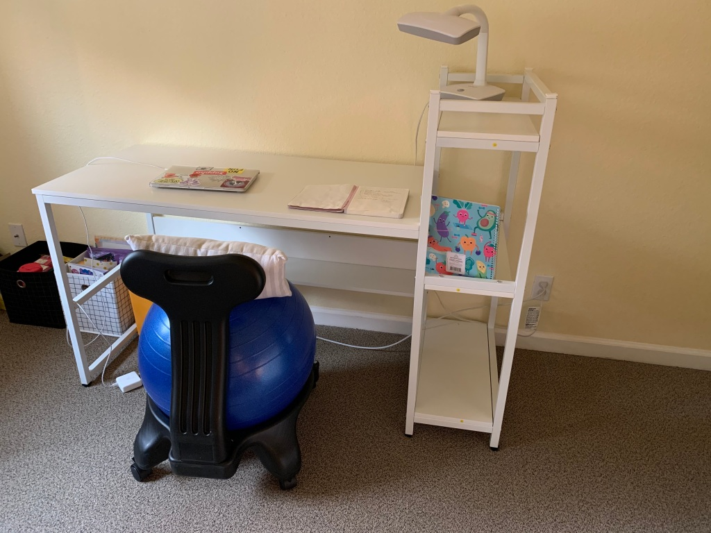 A white wayfair desk with attached bookcase. On the bookcase is a white desk lamp and a notebook. On the desk is a laptop and planner. In front of the desk is a yoga ball chair topped with a back pillow.
